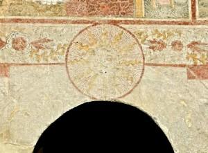 Au-dessus du portail de la chapelle on voit un cercle radieux portant le monogramme du Christ, autour une décoration floréale et sur les côtés le armoiries des Challant
